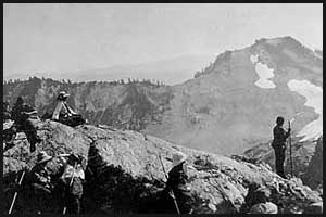 Men and women resting on rocks during climb of Mount Christie