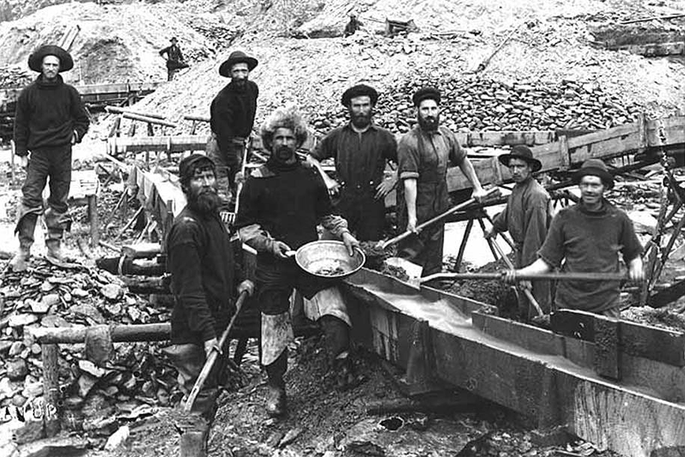 Gold mining operation showing miners using gold pan and a sluice, location unknown, ca. 1898