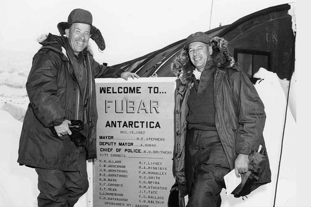 Senator Henry M. Jackson and Captain Heaman standing with a sign that says Welcome to...Fubar Antarctica, at Marble Point Base, Antarctica, October 16, 1959