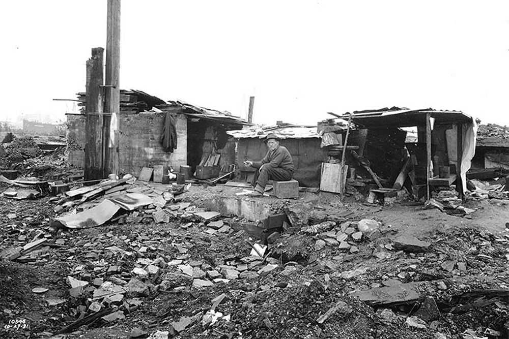 Homeless man sitting in front of shack in shantytown known as Hooverville, Seattle, Washington, October 27, 1931