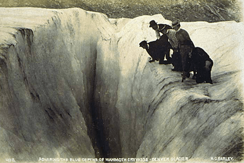 Excursion party at Denver Glacier peering into a crevasse, Alaska, ca. 1900.