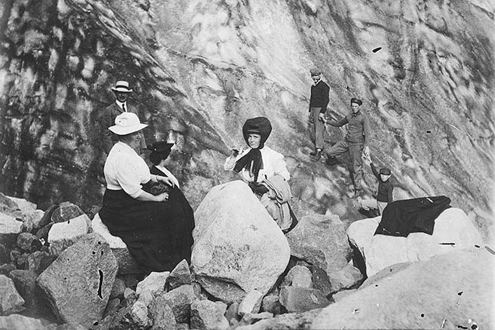 Hikers including two women, one of them Mrs. H. M. Sarvant, resting by boulders, Mount Rainier, August 14, 1908